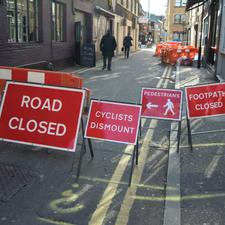 Exhibit D is a simply ridiculous collection of signs. 'Road Closed' would be quite enough on its own, with pedestrians and cyclists being perfectly capable of responding to the temporary circumstances without this 'help'. Of course, cyclists do not dismount, nor do they need to.