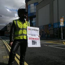 A motorcyclist protests against the bus lane