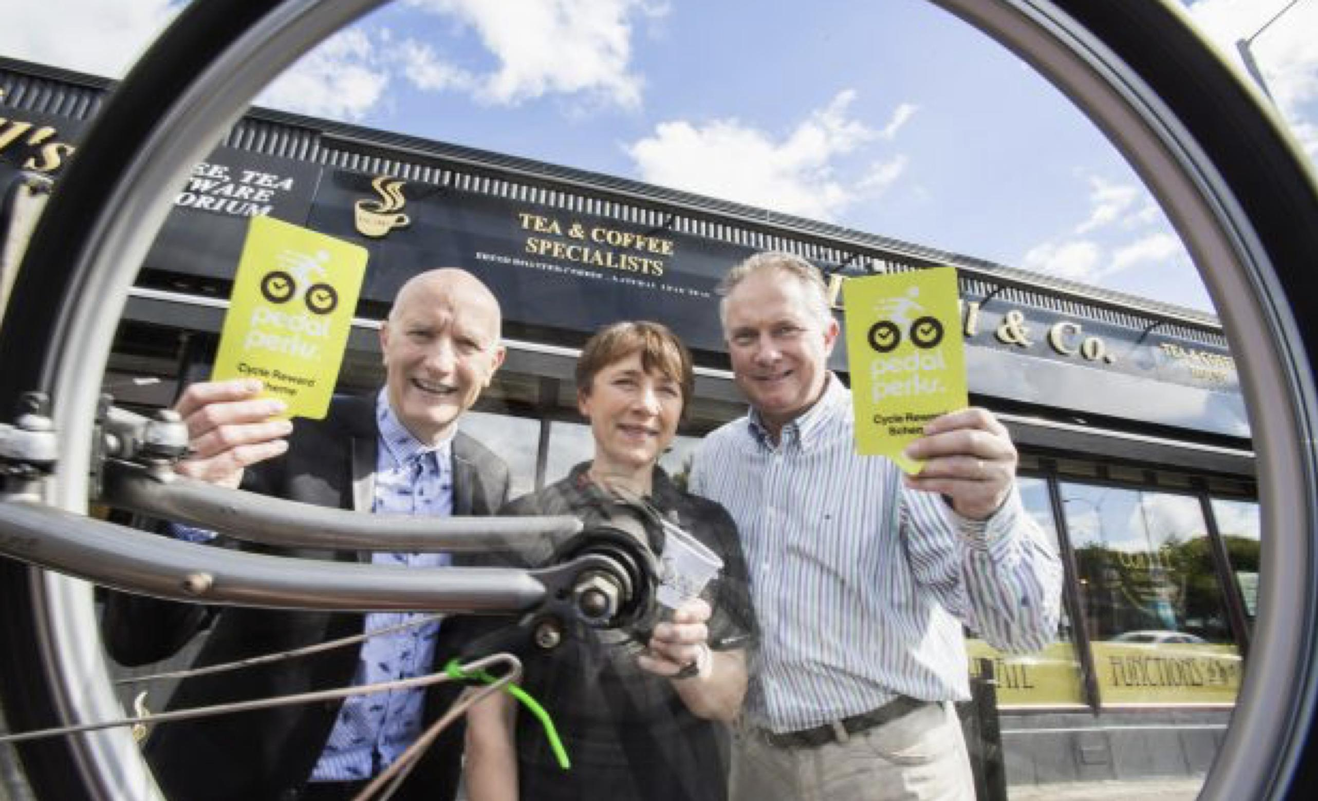 Colin Neill of Hospitality Ulster, Pamela Grove-White of Sustrans and Robert Bell, owner of SD Bells café in East Belfast launch the Pedal Perks cycling loyalty scheme