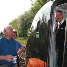 The owner of the cafe at Bridghouse station greets the driver of the first train to London 