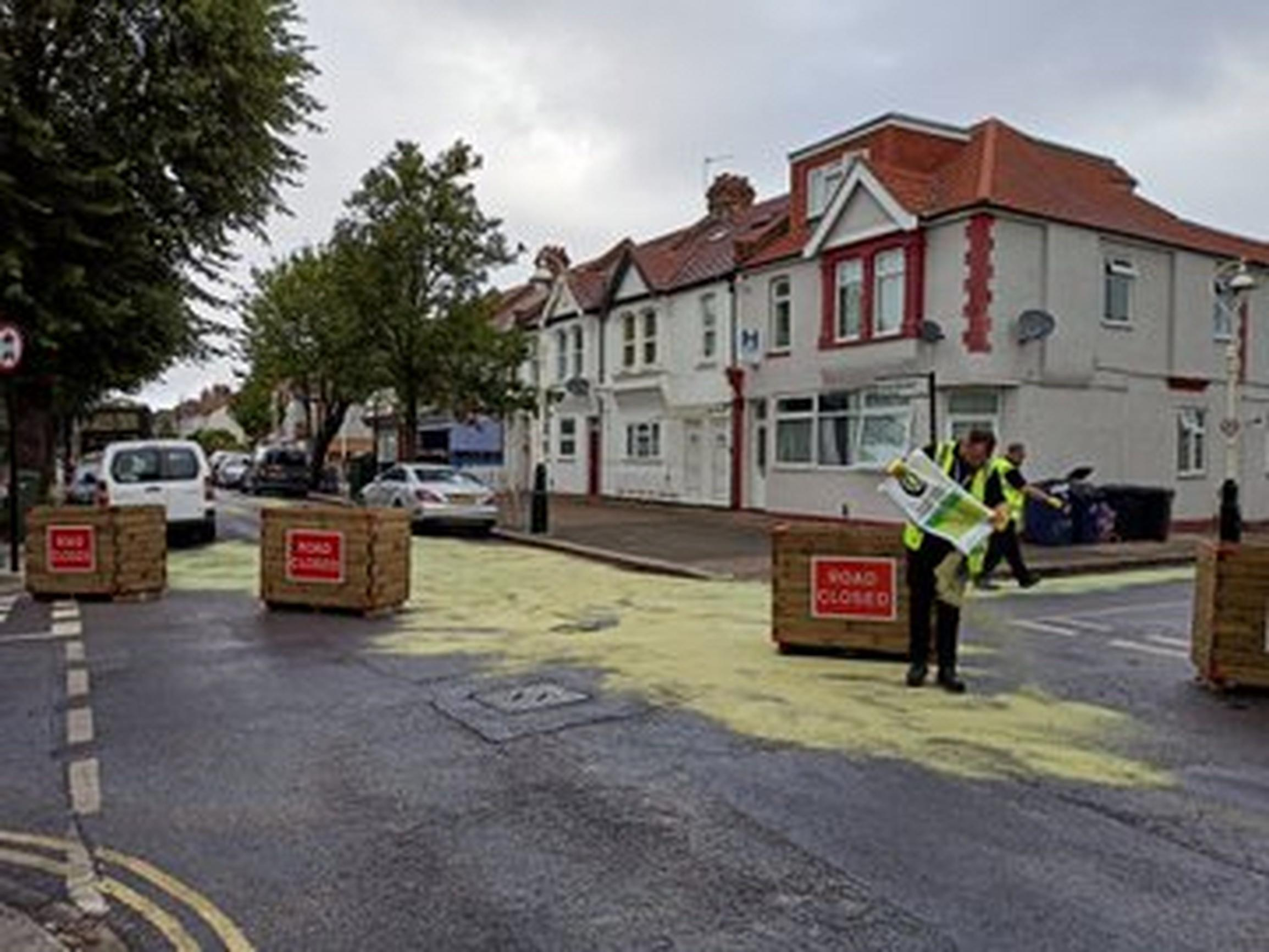 Yellow sawdust is laid on a temporary modal filter in Ealing after oil was poured across the road